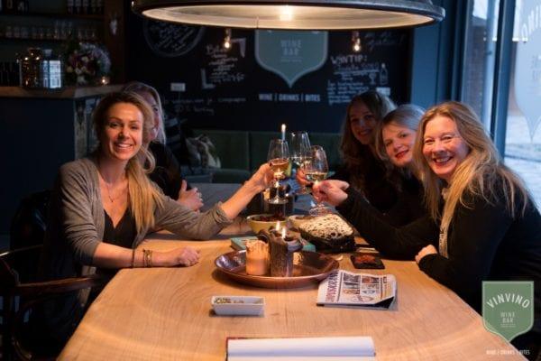 5 lachende dames aan 4 meter boomstamtafel